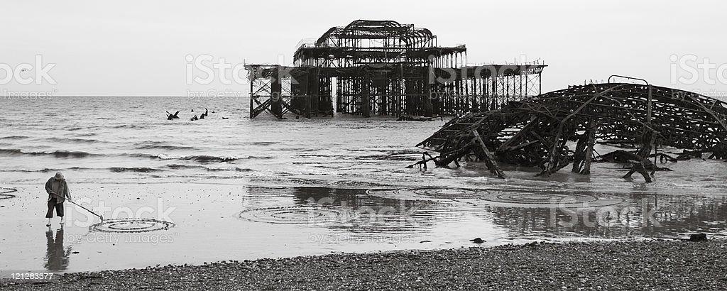 Man draws circles on the sand in Brighton, England stock photo