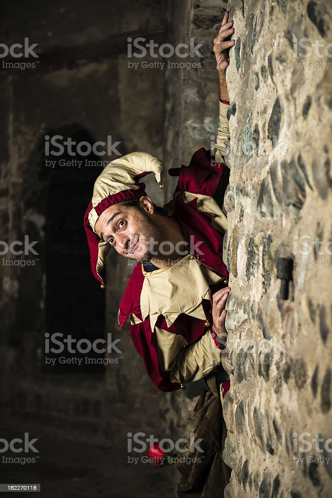 Man dressed as jester peering around corner of stone wall stock photo