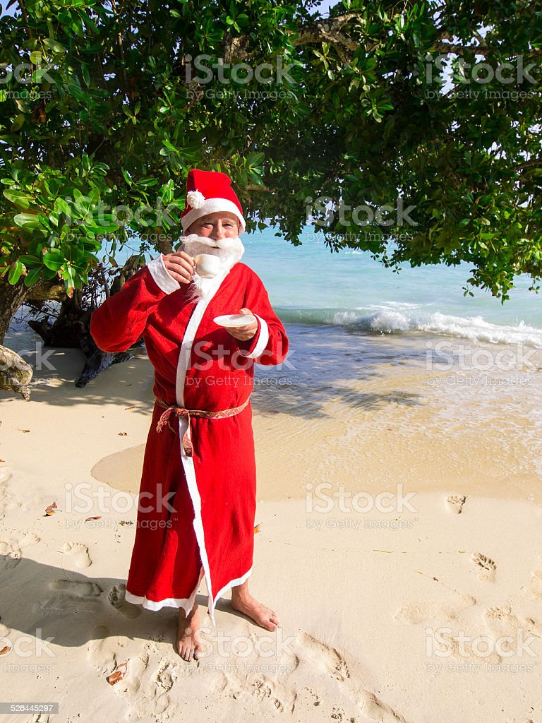 man dressed as Santa Claus sipping coffee on tropical beach stock photo