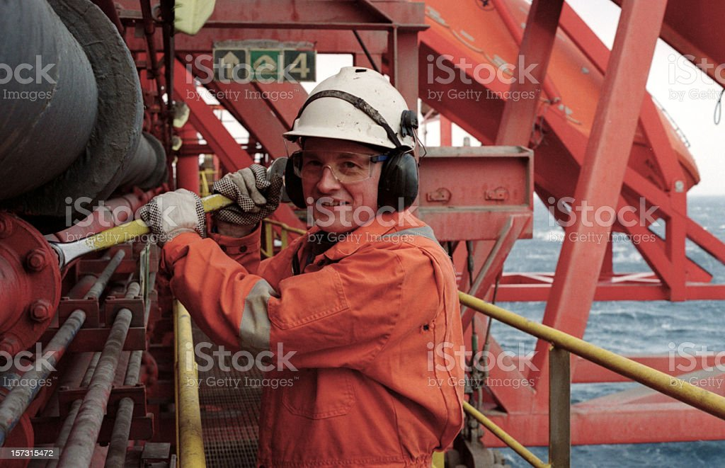 Man Dressed in Orange Working on an Oil Rig stock photo