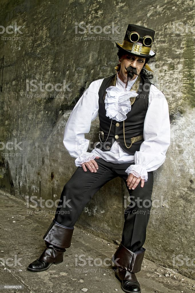 man dressed in steampunk, victorian clothing, dark wall background stock photo