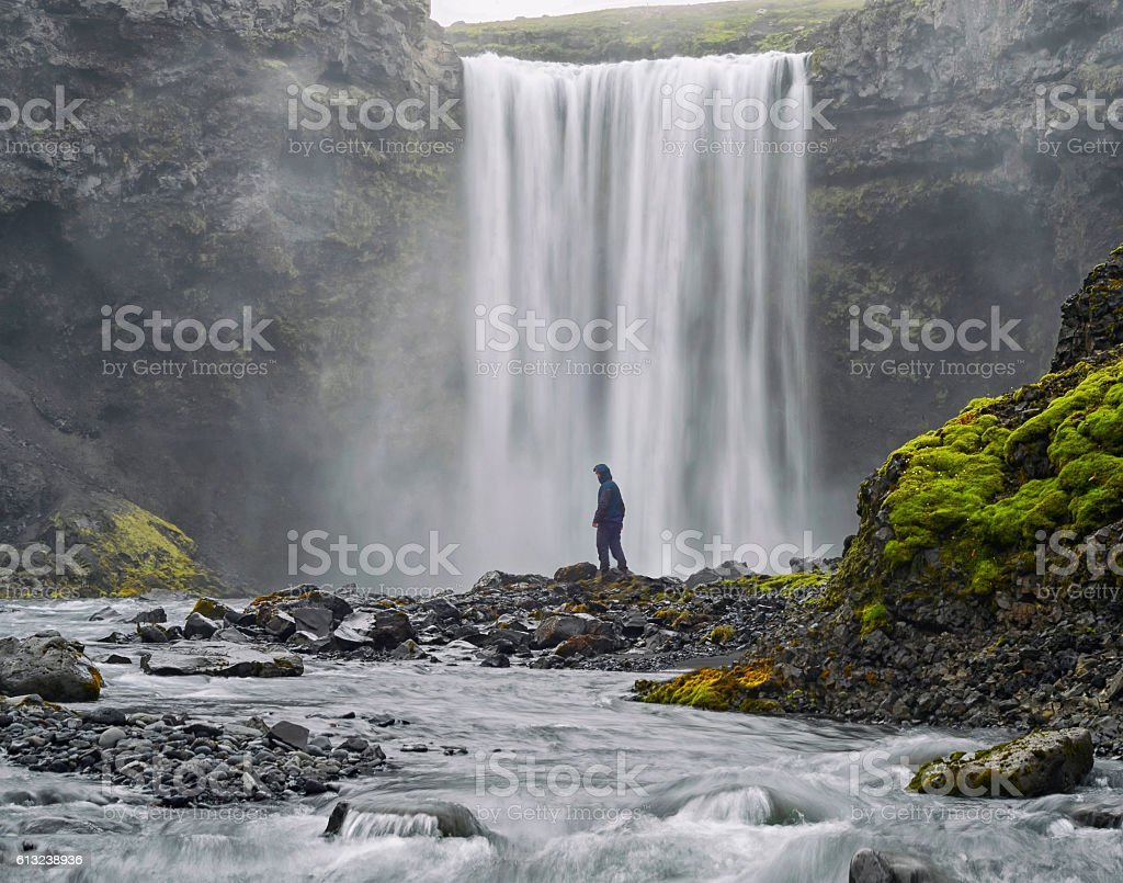 Man dressed  standing at the base of a waterfall stock photo