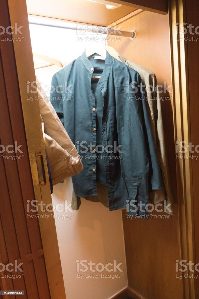 Man dresses hanging in wooden wardrobe stock photo