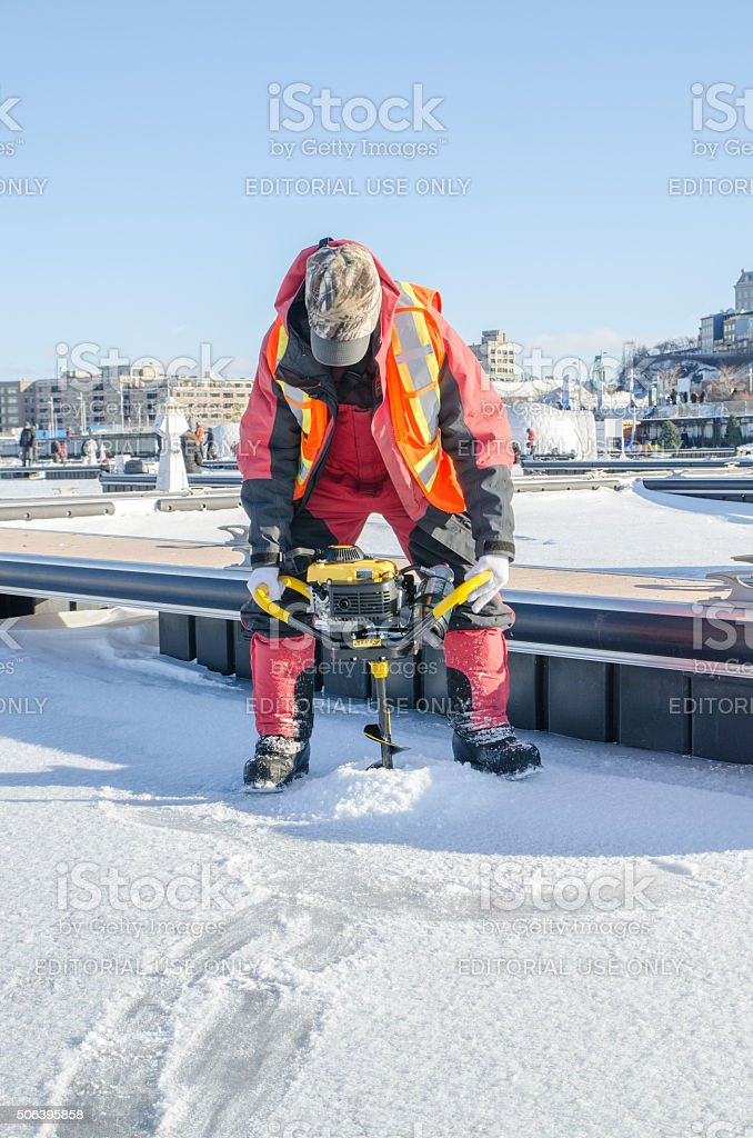 Man drilling a hole in ice for fishing stock photo