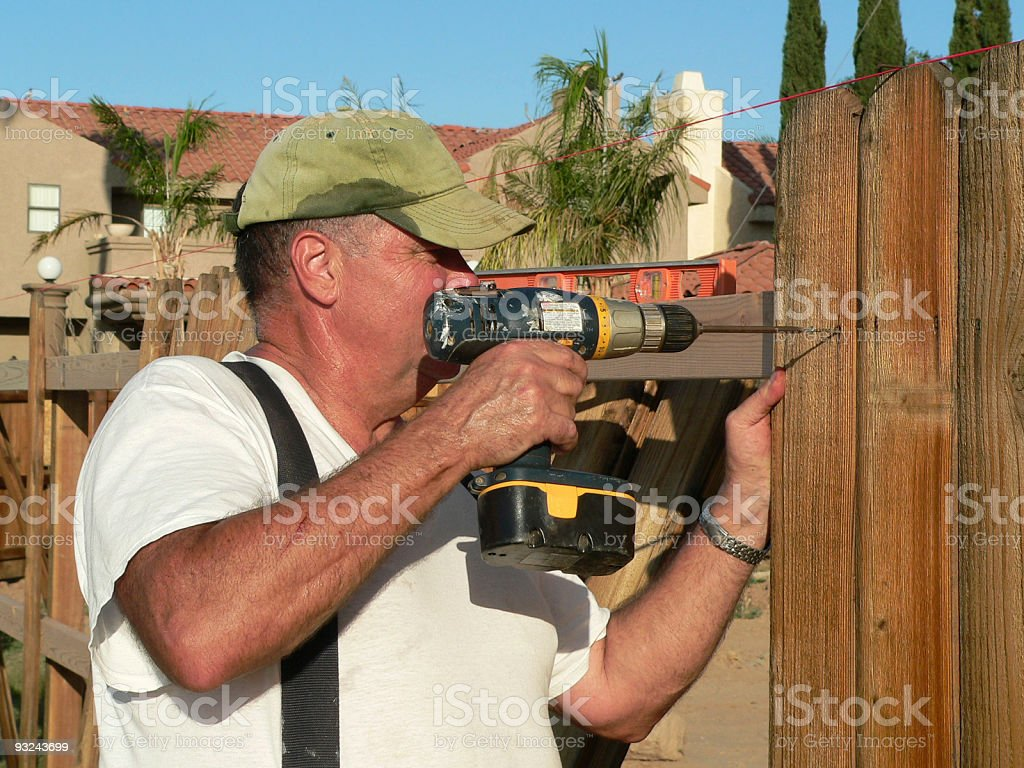 Man drilling screw into cedar fence board royalty-free stock photo