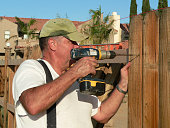 Man drilling screw into cedar fence board