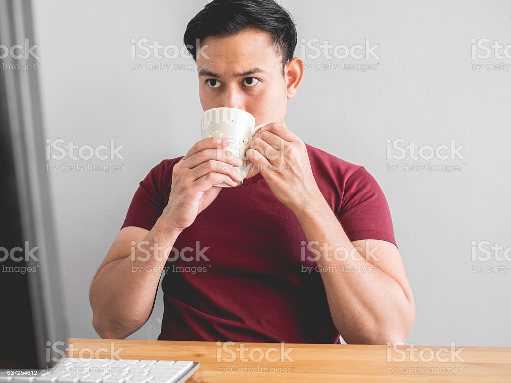 Asian man drink coffee on desk for work idea.