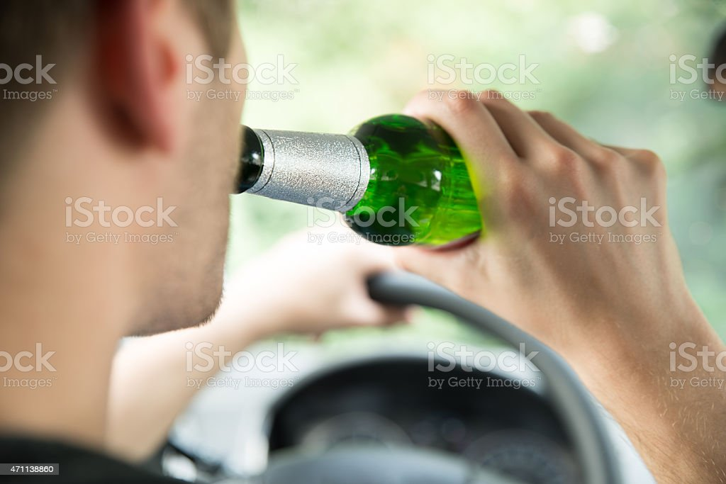 Man Drinking Alcohol While Driving Car stock photo