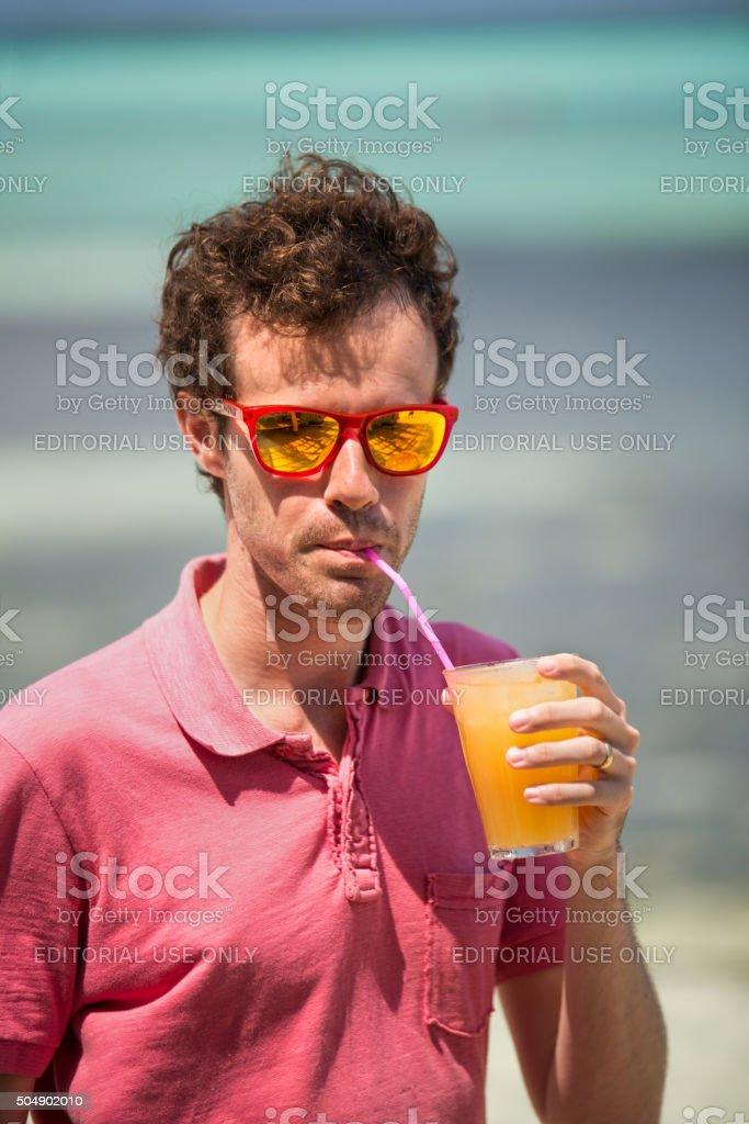 Man drinking an orange cocktail royalty-free stock photo