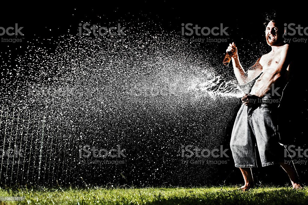 Man Drinking and Spraying Beer All Over Lawn at Night royalty-free stock photo