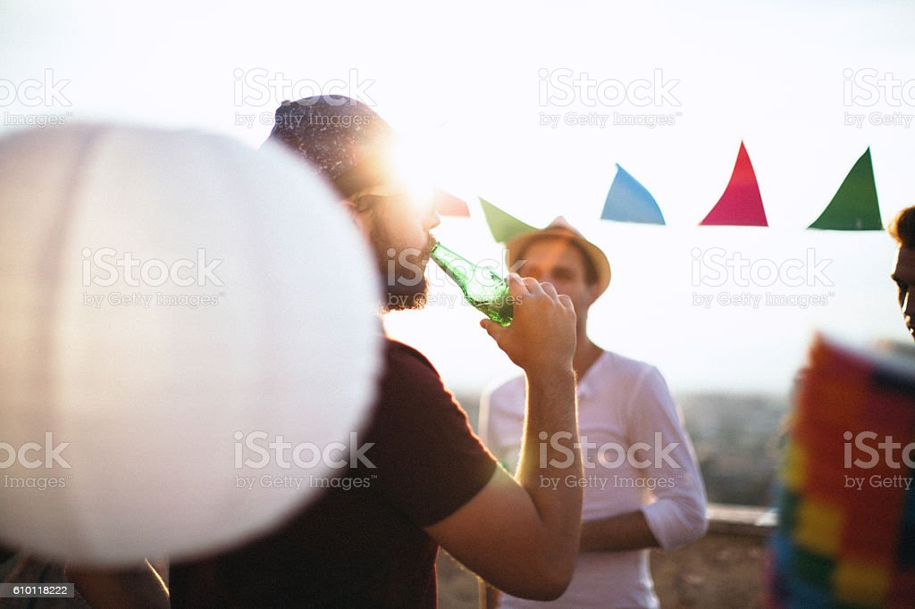 Man drinking beer on party with friends stock photo