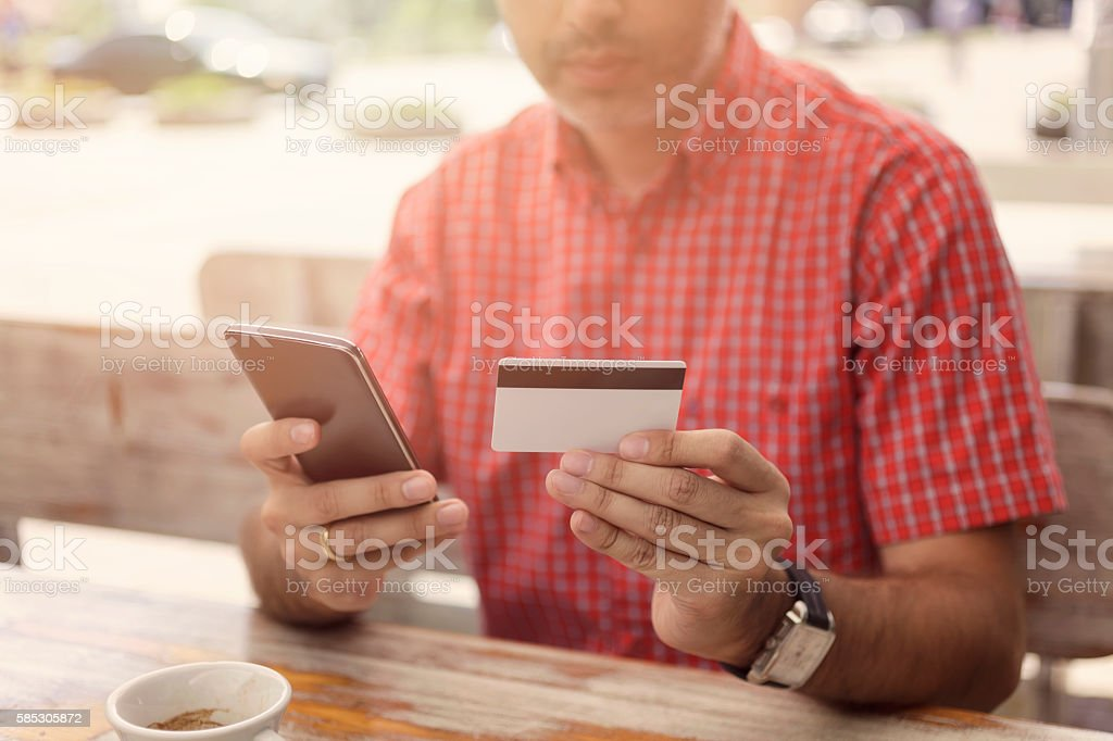 Man Drinking Coffee and Making Mobile Payment With Smartphone stock photo
