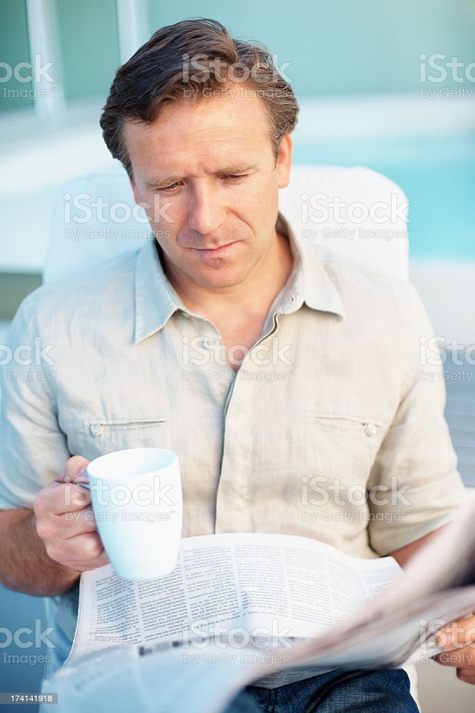 Man drinking coffee while reading a newspaper stock photo