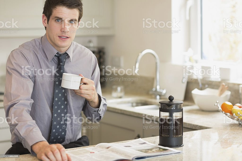 Man drinking coffee while reading newspaper royalty-free stock photo