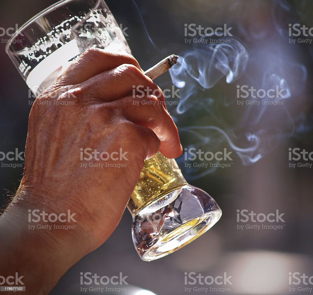 Man drinking glass of beer and smoking cigarettes royalty-free stock photo