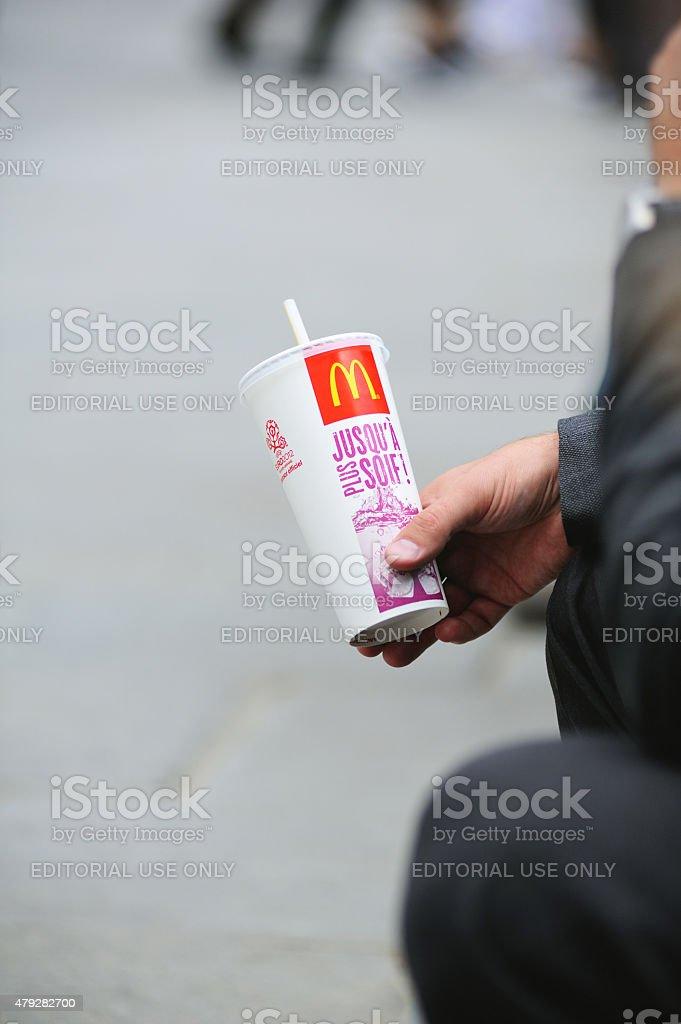 Man drinking McDonalds soda on a stret backgroun stock photo