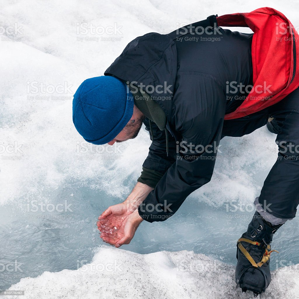 Man drinking water from a stream on Franz Josef Glacier stock photo