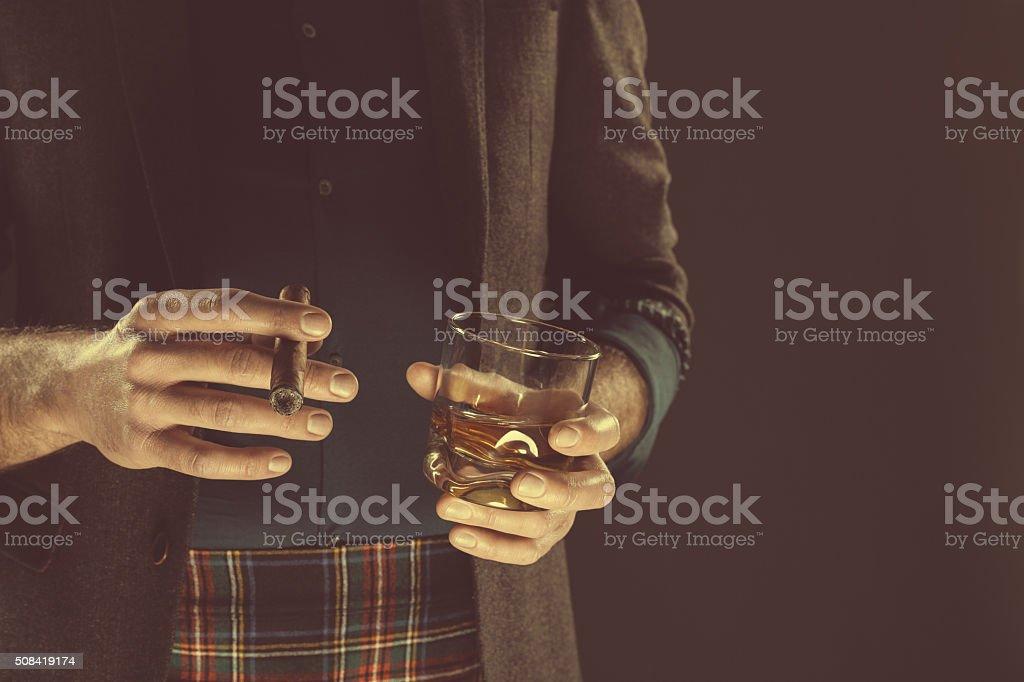 Man drinking whiskey and smoking cigar, close up of hands stock photo