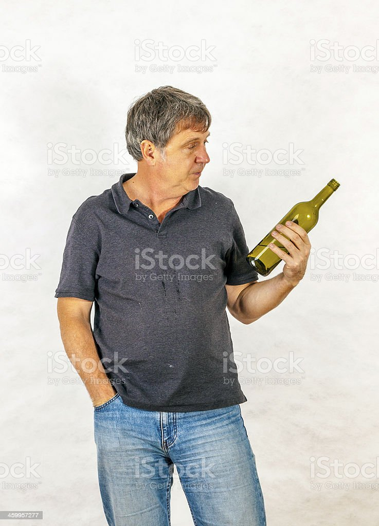 man drinks alcohol out of a bottle stock photo