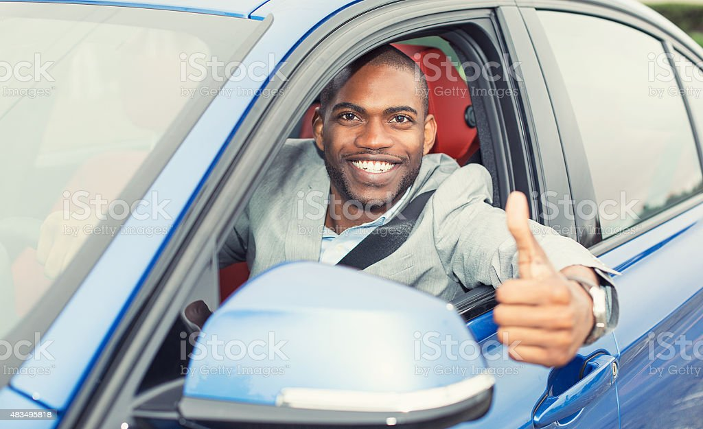 Man driver happy showing thumbs up coming out of car stock photo