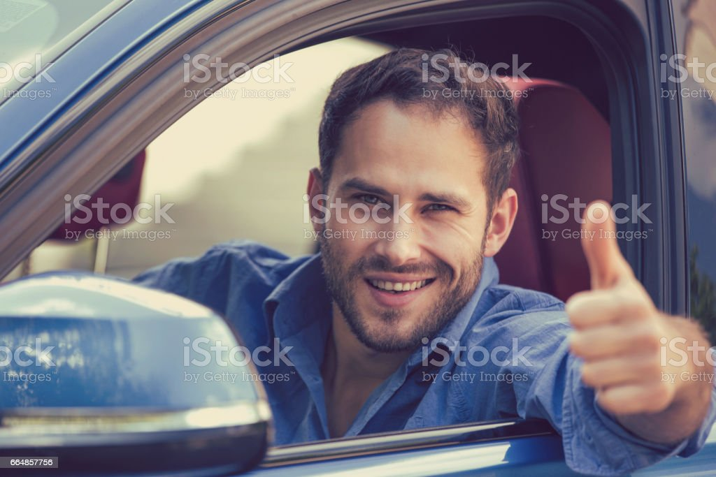 Man driver happy smiling showing thumbs up driving sports blue car on a city street outside background stock photo