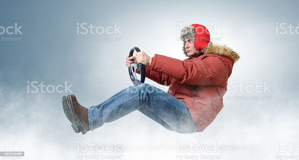 Man driver in a red cap with a steering wheel stock photo