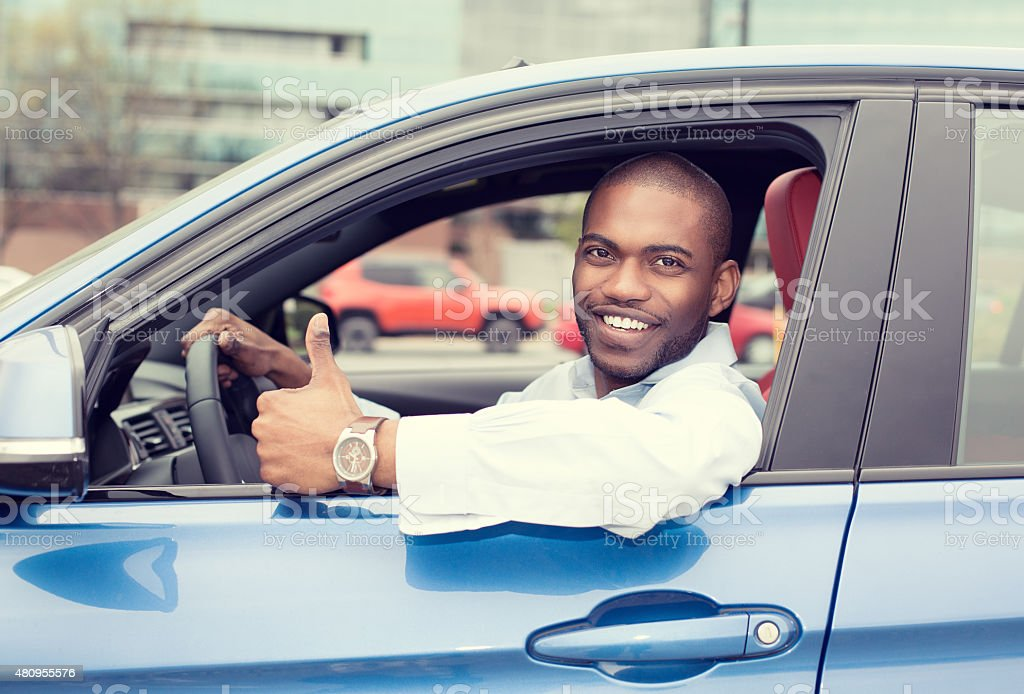 Man driver showing thumbs up driving sport blue car stock photo