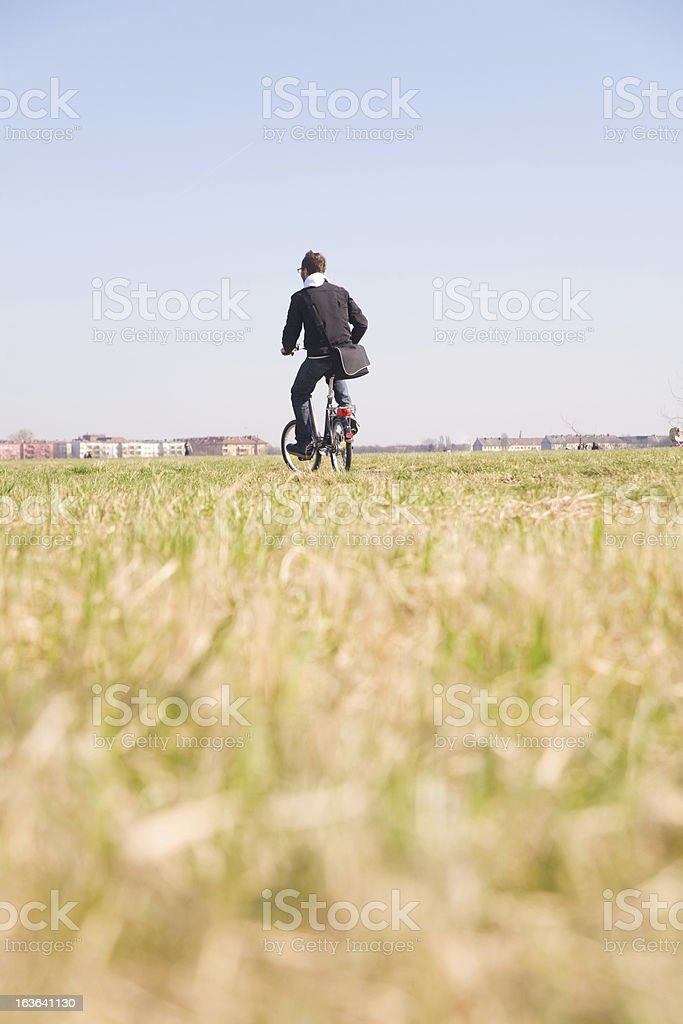 Man drives away on bicycle royalty-free stock photo