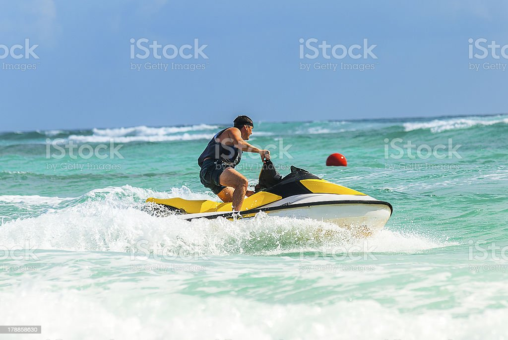 Man drives yellow jet ski on turquoise ocean on a blue day stock photo