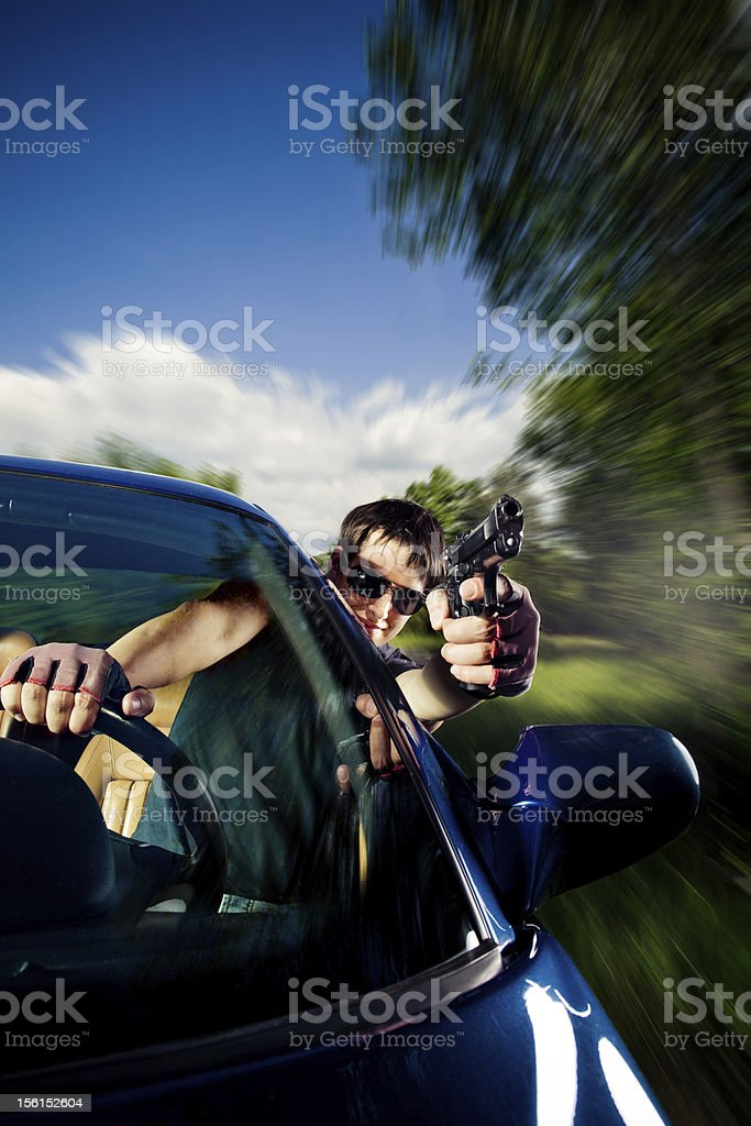 Man driving a car and shooting stock photo