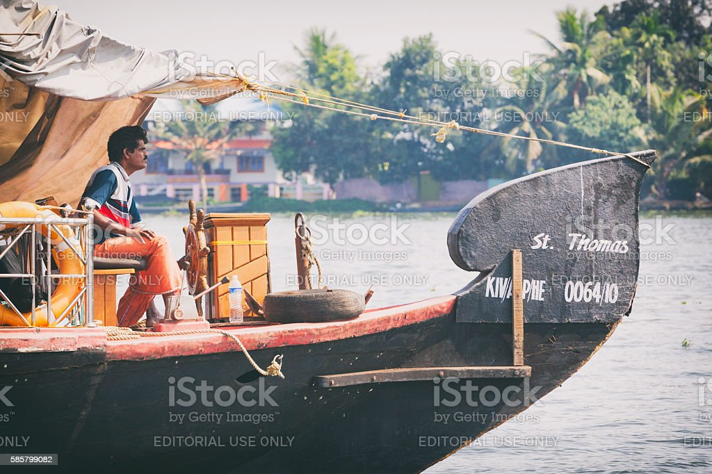 Man driving a Houseboat on the Kerala Backwaters in India stock photo