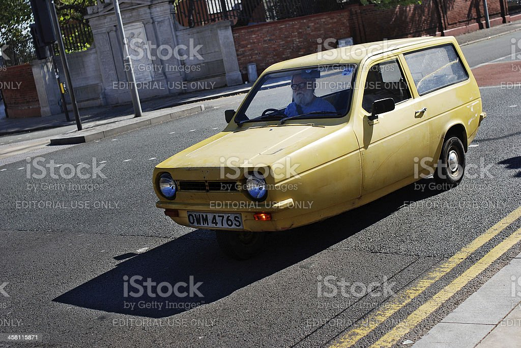 Man driving a yellow Reliant Robin stock photo