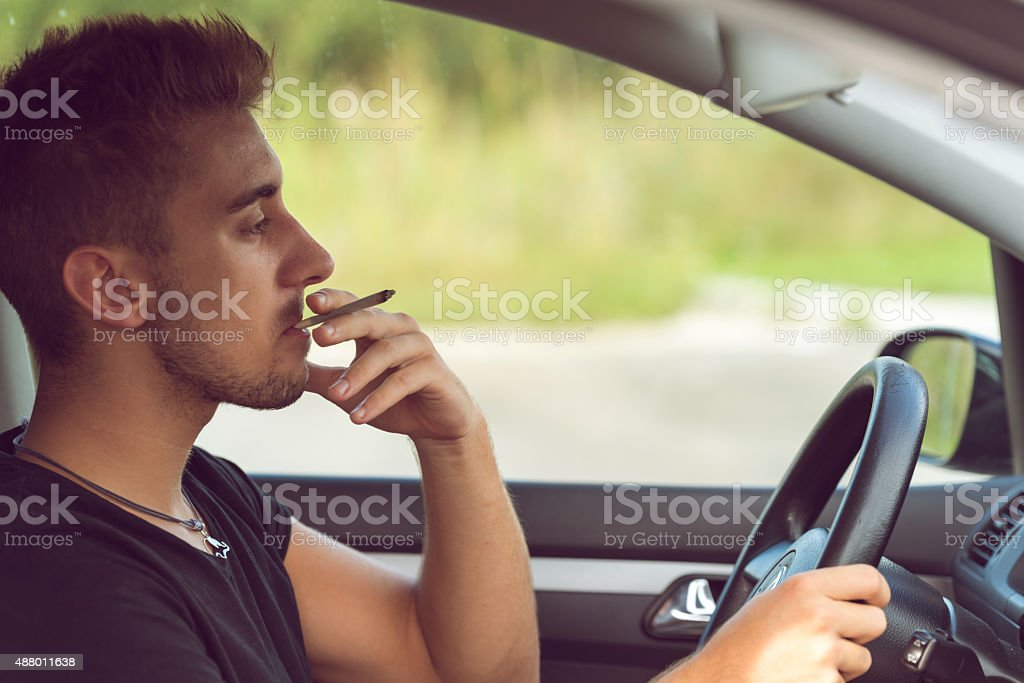 Man driving and smoking joint stock photo