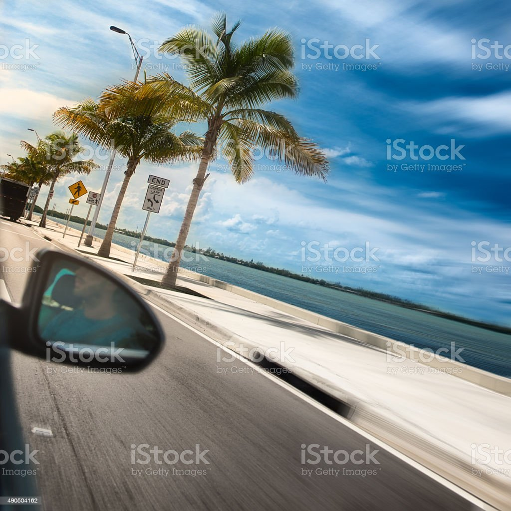 Man driving car across paradise road with palms and ocean stock photo