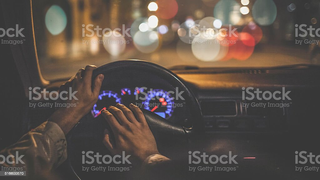 Man driving car at night stock photo