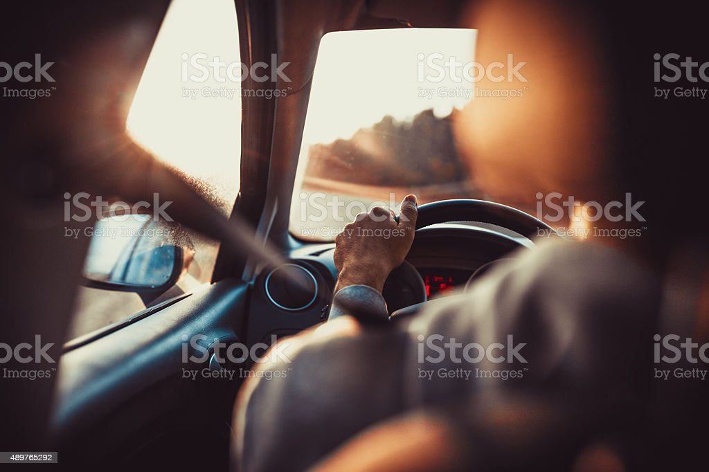 Man driving car, hand on steering wheel, looking at the road...