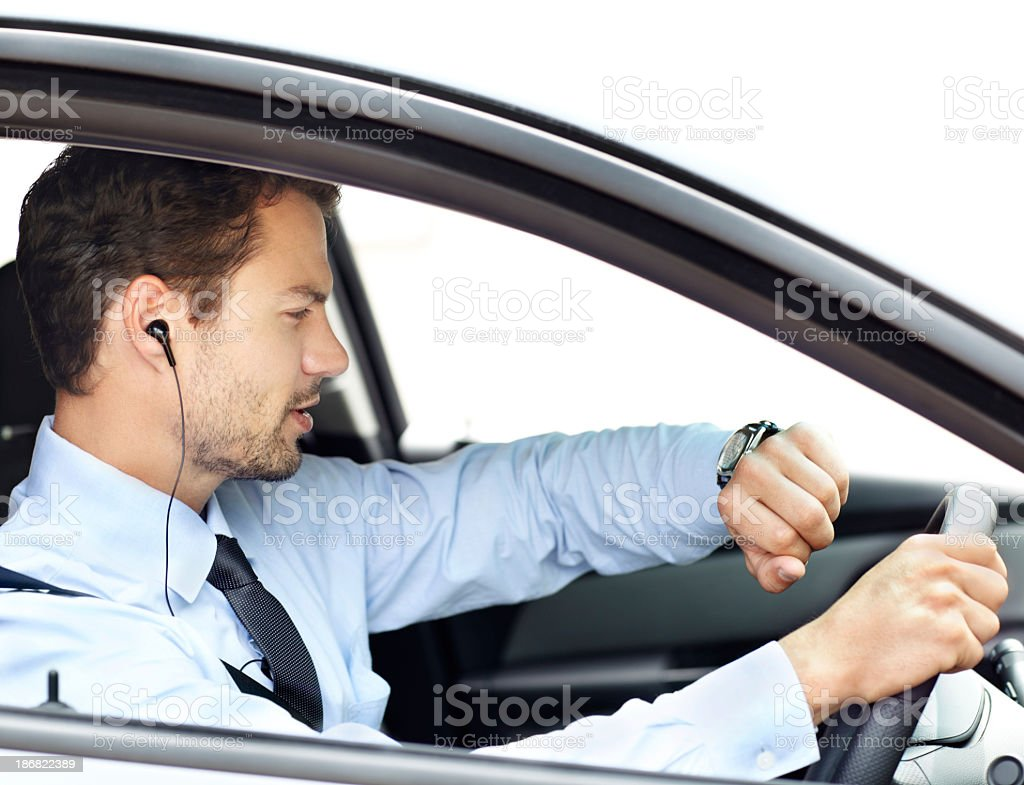 Man driving car with earphones on, looking at wrist watch royalty-free stock photo
