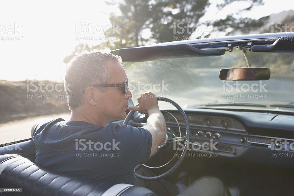 Man driving classic convertible car stock photo