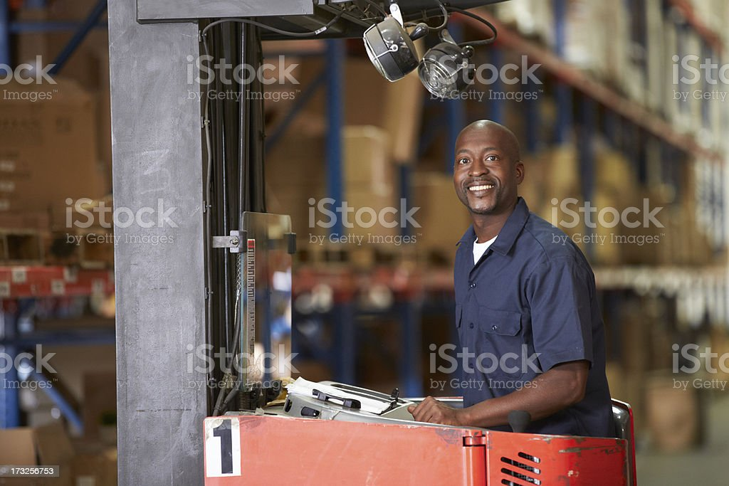 Man Driving Fork Lift Truck In Warehouse stock photo