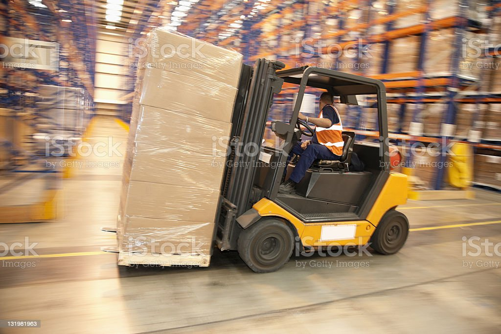 Man driving forklift in warehouse royalty-free stock photo