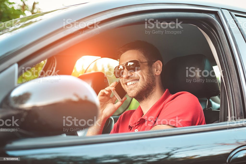 Man driving his car and speaking on the cellphone stock photo