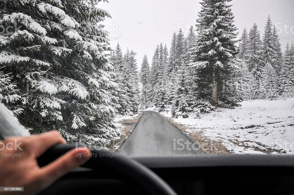Man Driving in a Snow through mountain forest stock photo
