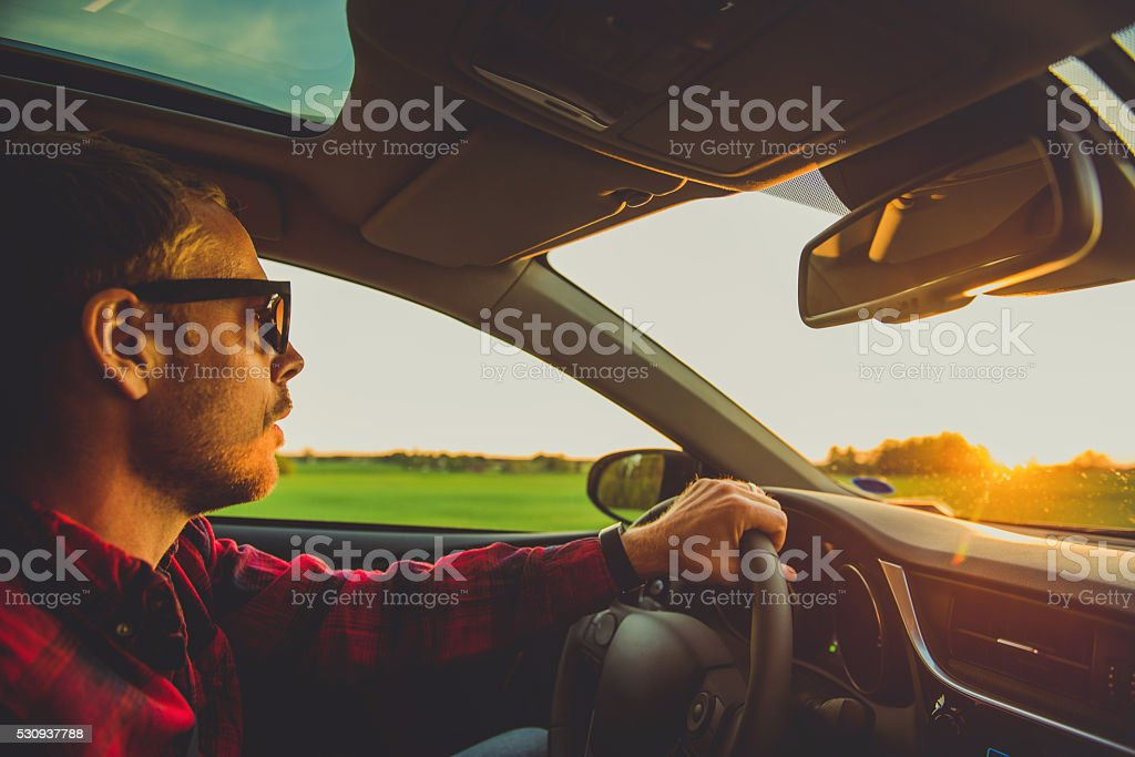 Man driving in sunset stock photo