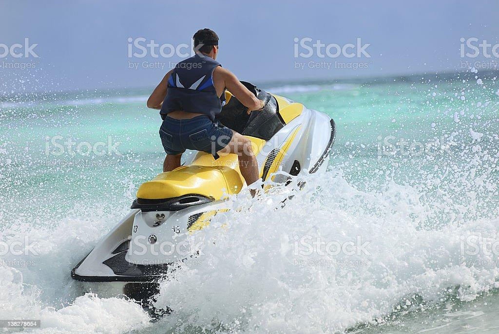 Man driving jet ski making waves stock photo
