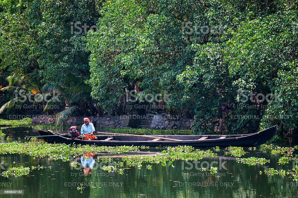 Man driving Kettuvallam on the Kerala Backwaters in India stock photo