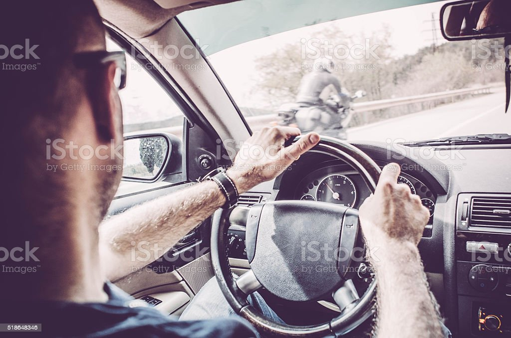 Man driving - motorbike overtaking a car stock photo