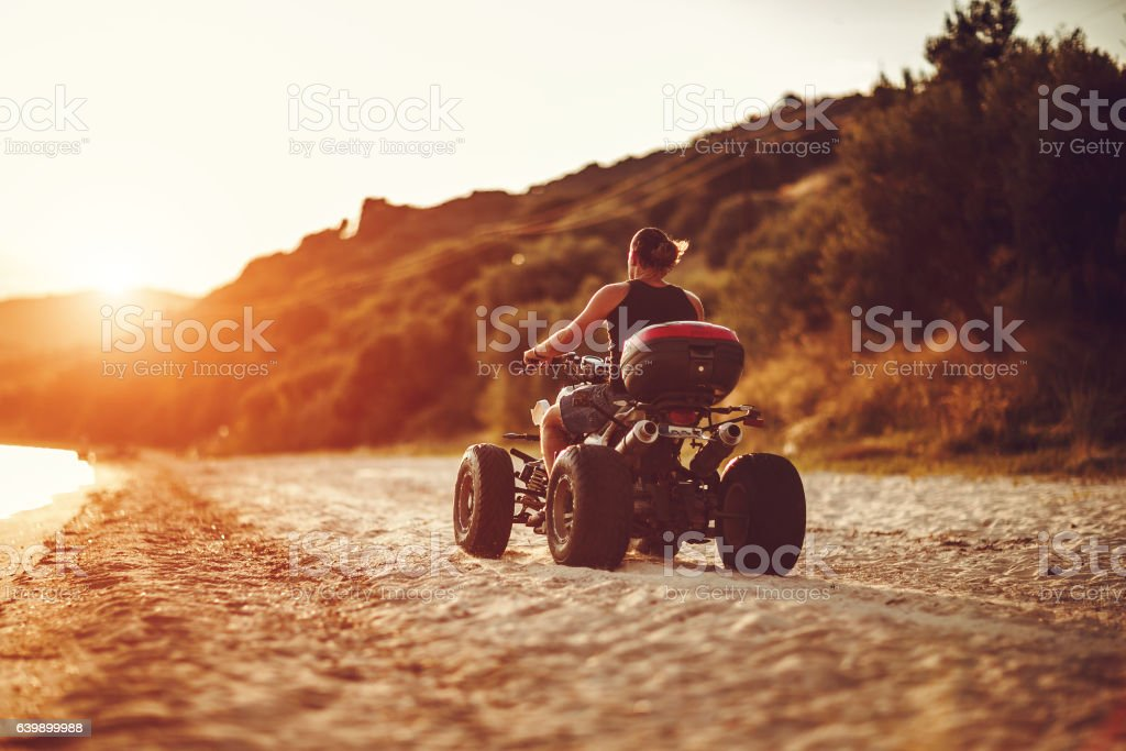 Man driving quadbike in sunset stock photo