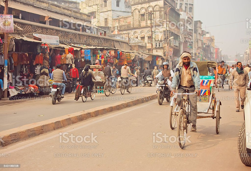Man driving rickshaw bicycle on busy road with many stores stock photo