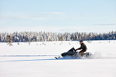 Man driving snowmobile in Finland