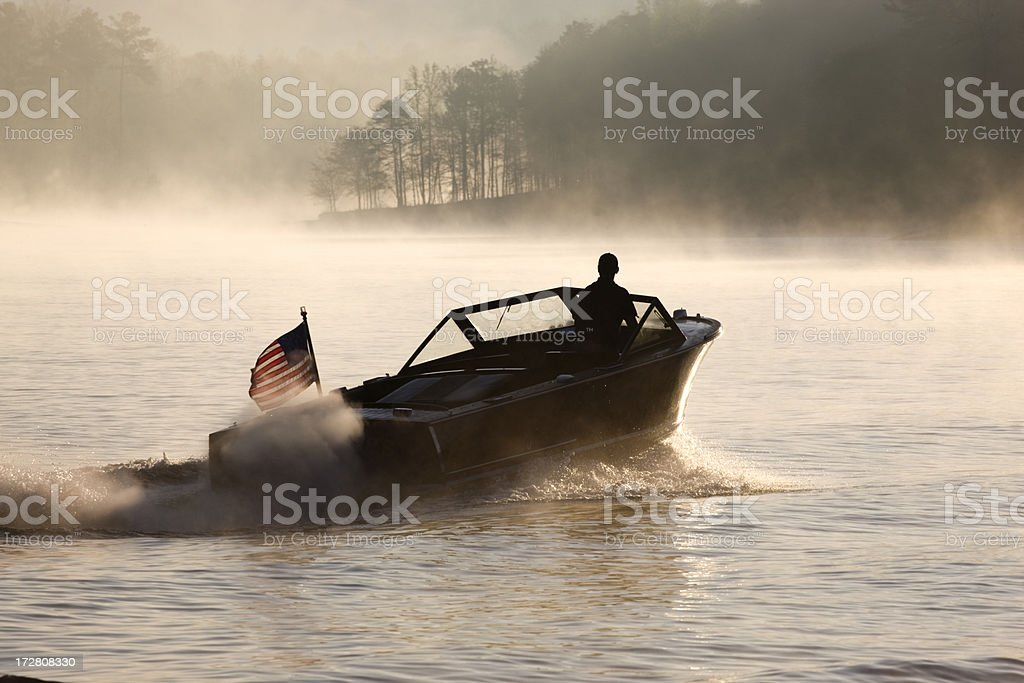 Man driving speedboat alone on hazy foggy lake at dawn stock photo